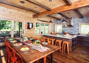 Log home kitchen with bright pops of orange, red and yellow at the rustic dining room table. An island with 4 orange stools and modern kitchen is in the background.