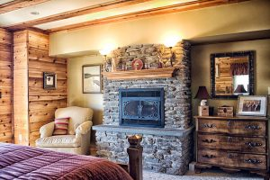Log home bedroom with a muted pink bedspread, fireplace, ivory chair and dresser.